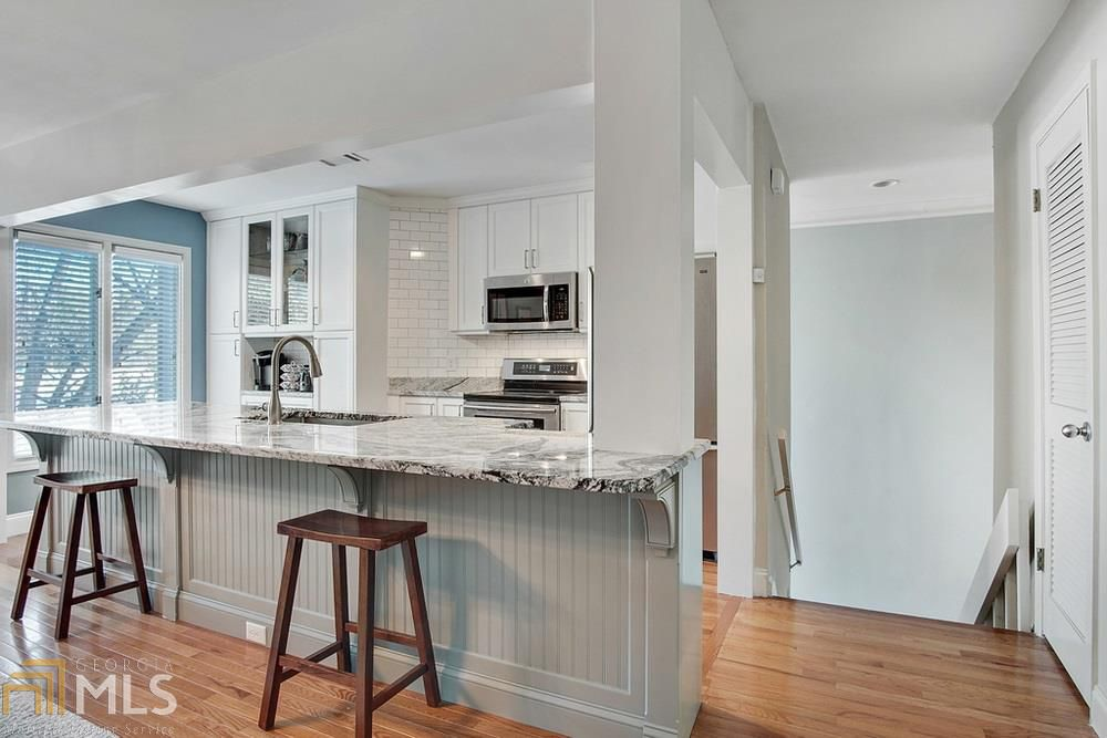 Looking into kitchen over a bar with a staircase on the right.