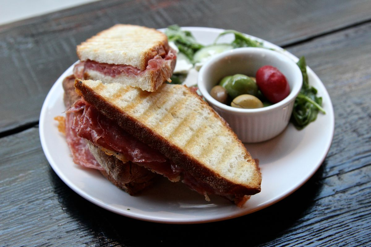 A prosciutto sandwich with a side of colorful olives