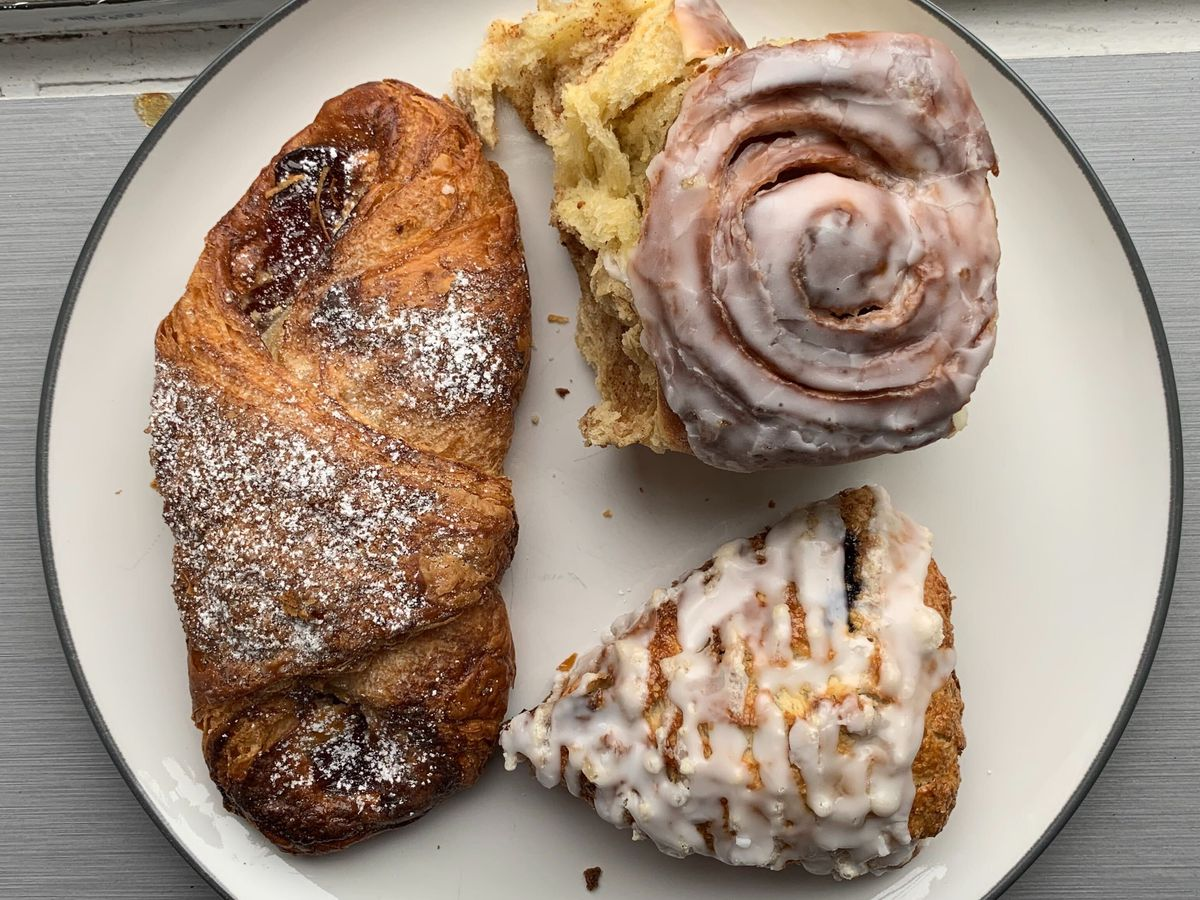Three pastries placed on a white plate near a window sill
