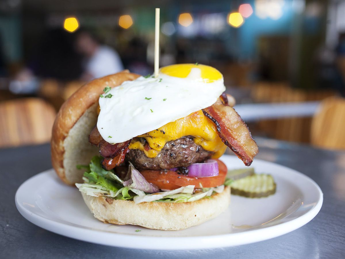 A thick cheeseburger on tomato, lettuce, onions, and a bun, topped with a fried egg and pierced with a toothpick, with the top bun and pickle slices nearby