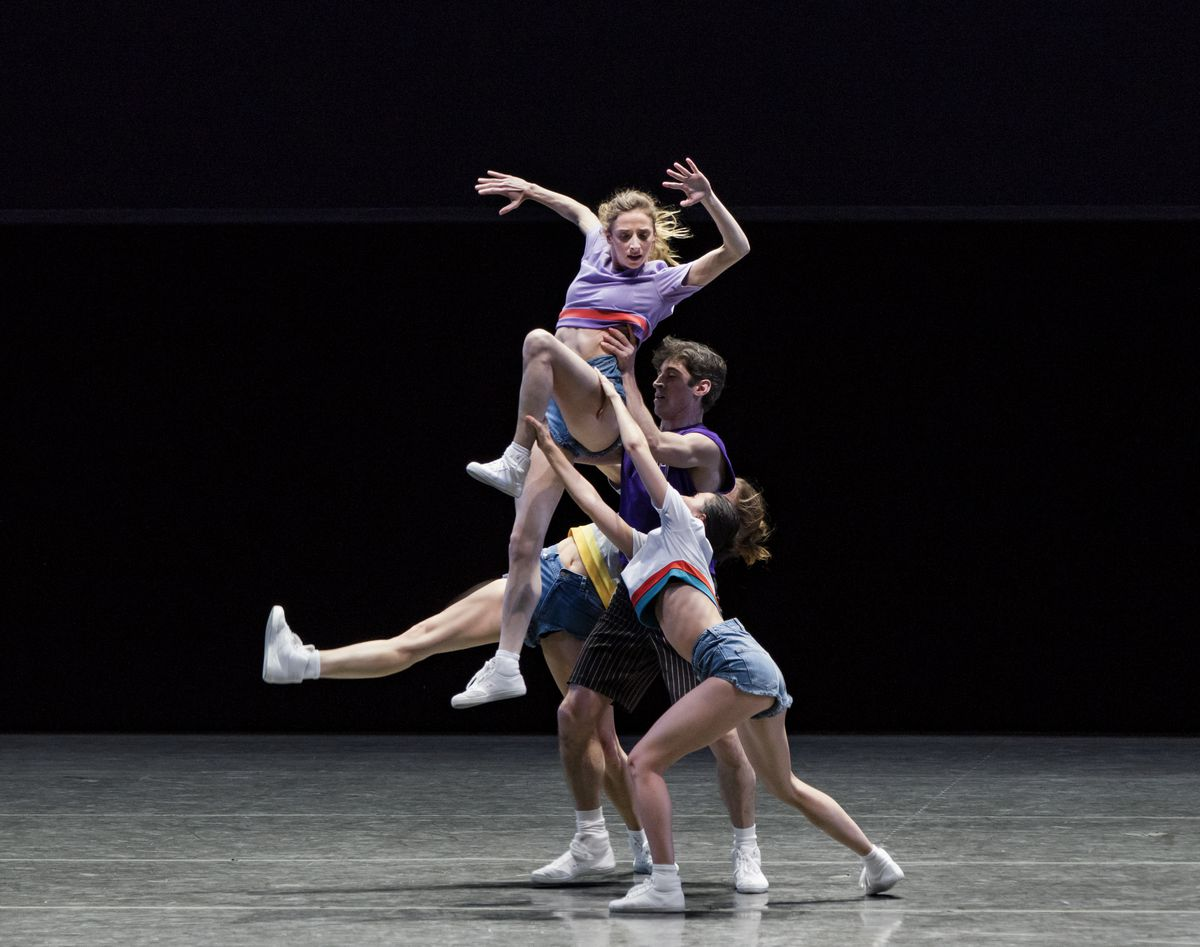 Dancers wearing brightly colored shorts and T-shirts lift a woman up.