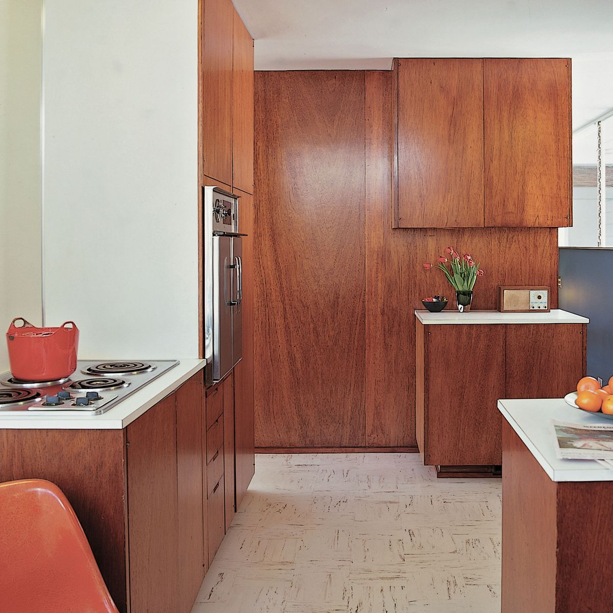 A room with dark wood cabinets and white countertops. An electric stove can be seen on the left