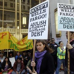 Demonstrators march and block a side entrance to the Wells Fargo shareholders meeting in San Francisco, Tuesday, April 24, 2012. Police guarded the entrance to the annual meeting of Wells Fargo shareholders on Tuesday as protesters associated with the Occupy Wall Street movement protested the gathering.
