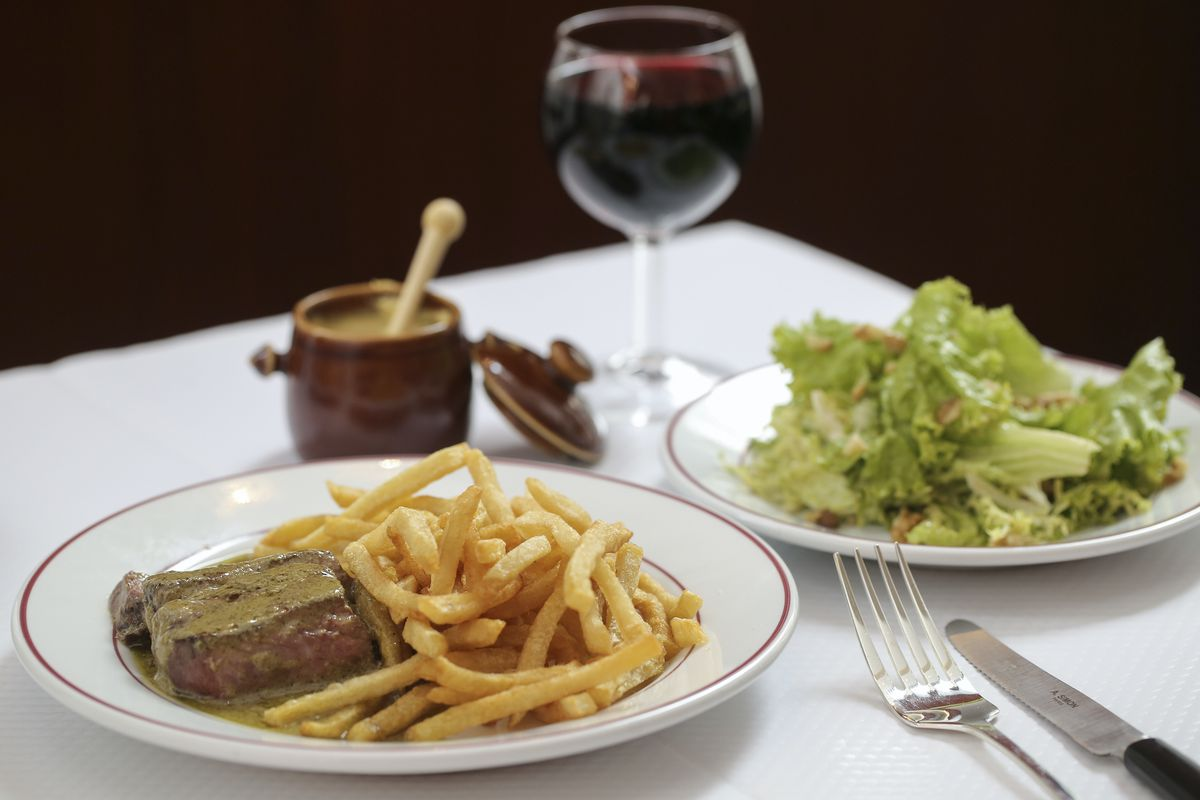 A plate of French bistro steak frites with sauce.