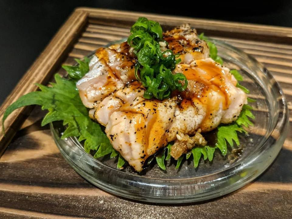 Several pieces of seared salmon belly are nestled on a round clear plate on a wooden tray