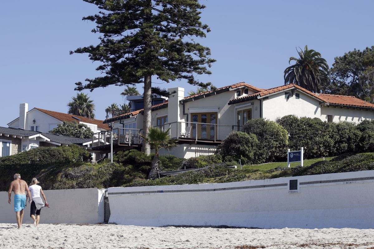 People walk along the beach in front of a home owned by Mitt Romney, and his wife Ann on Friday, Oct. 11, 2013, in La Jolla, Calif.