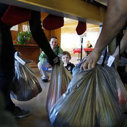 Danielle Andrus and her son Zech watch as bags of gifts are brought through the chimney for them during 2014 Operation Chimney Drop at Head Start in Salt Lake City, Monday, Dec. 15, 2014.