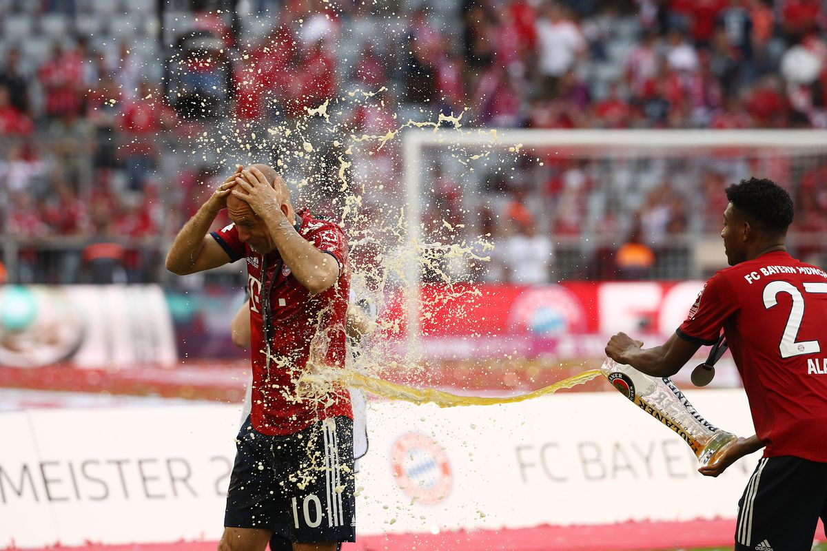 MUNICH, GERMANY - MAY 12: Arjen Robben of Bayern Muenchen (l) gets covered in bear by Kingsley Coman of Bayern Muenchen (r) during the Bundesliga match between FC Bayern Muenchen and VfB Stuttgart at Allianz Arena on May 12, 2018 in Munich, Germany.