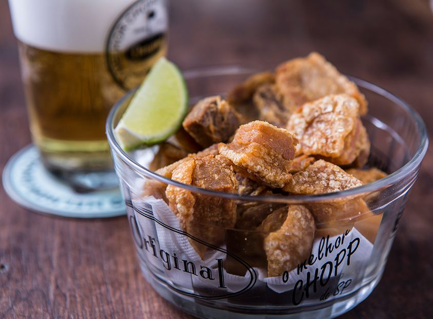 A glass bowl with the name Original on the side, is filled with chicharron and a lime wedge, beside a glass of beer blurred in the background