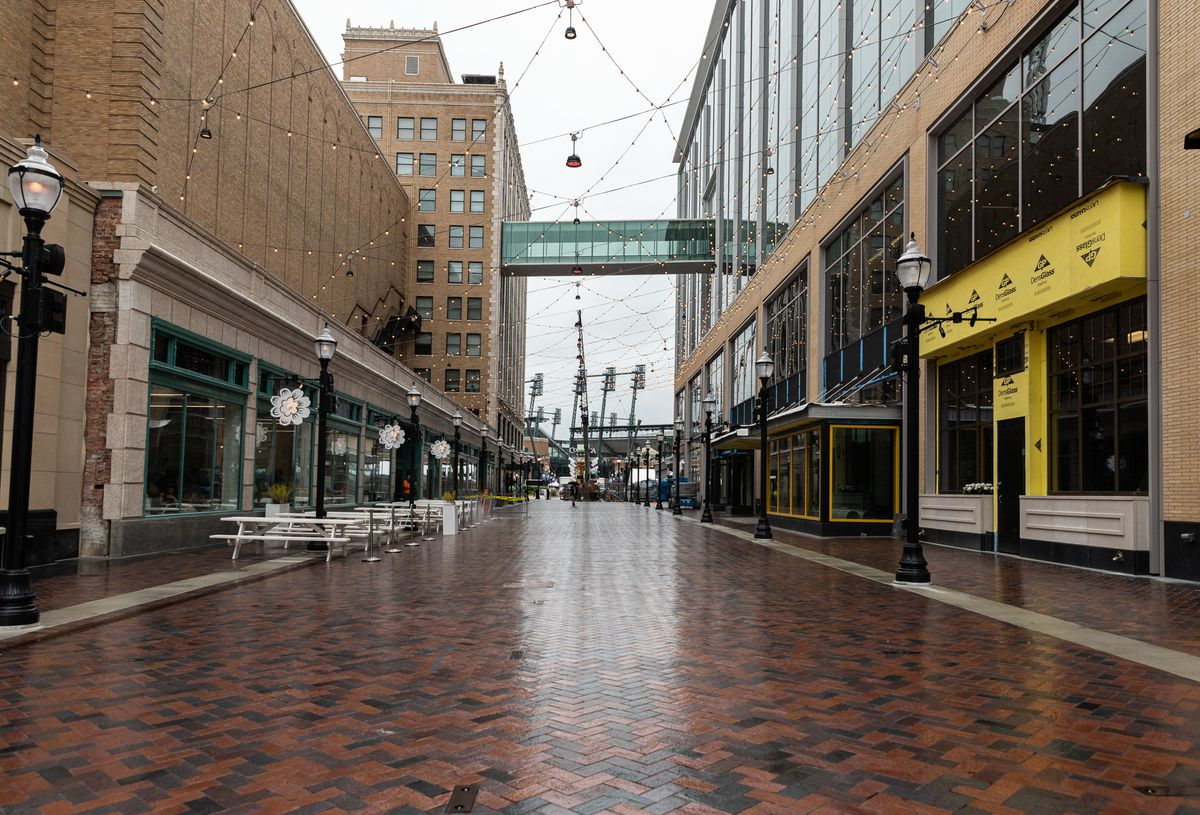 The the brick pedestrian road, now known as the Columbia Street promenade, is shown facing towards Comerica Park on a rainy day with the Frita Batidos patio picnic tables on the left.