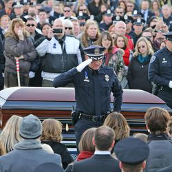 Salt Lake County Sheriff Jim salutes  Erika Barney, wife of slain Unified police officer Doug Barney, at the gravesite at the Orem City Cemetery on Monday, Jan. 25, 2016. Barney was killed in the line of duty on Jan. 17, 2016.