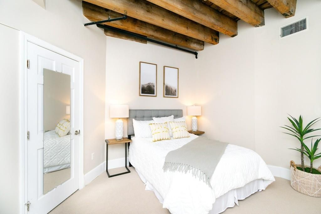 A bedroom with a beamed ceiling and the door to the bedroom is closed.