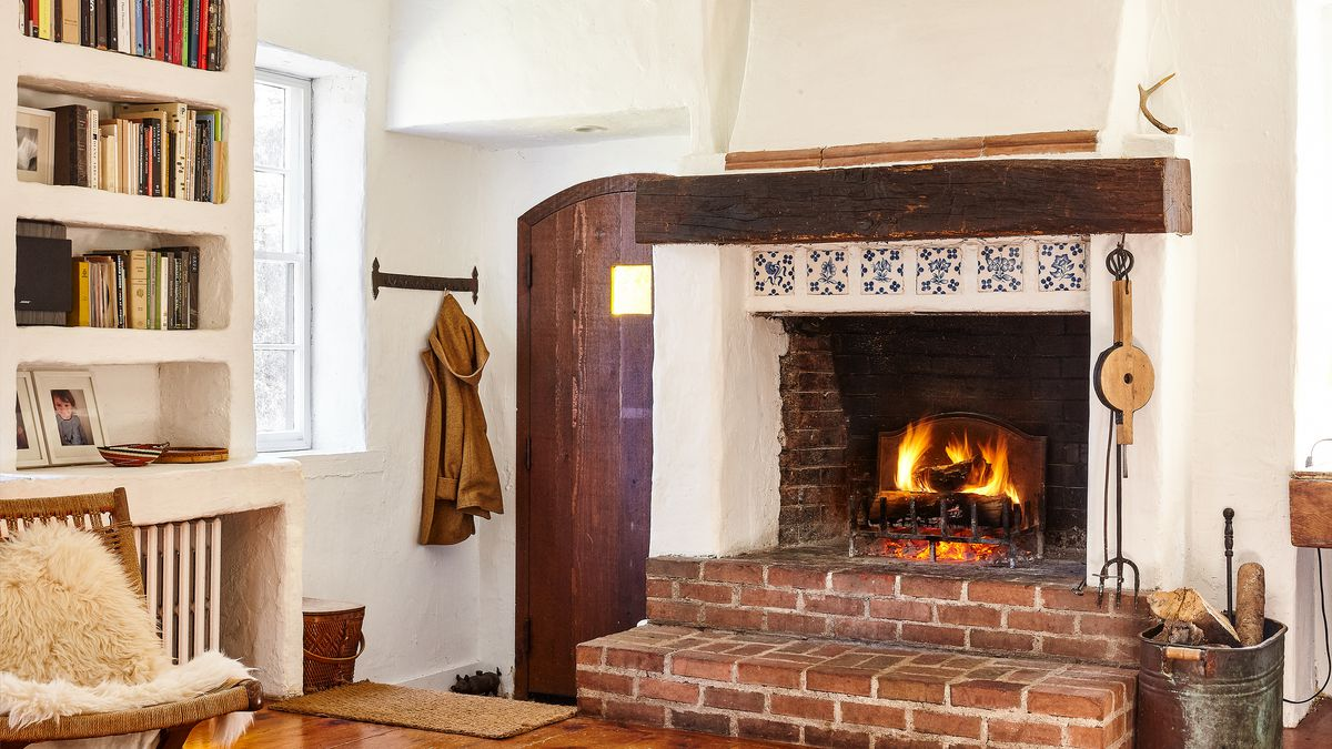 In a white room with a filled bookcase, wooden floors, and a shag-covered chair is a fireplace surrounded by brick.