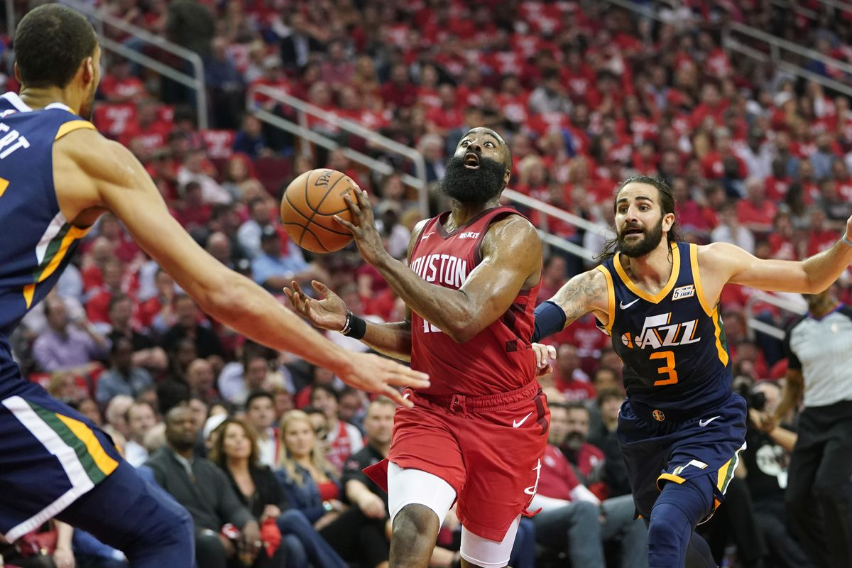 Houston Rockets guard Eric Gordon passes the ball as he drives against Utah Jazz center Rudy Gobert (27) and guard Ricky Rubio (3) during the first half of Game 2 of a first-round NBA basketball playoff series in Houston, Wednesday, April 17, 2019. (AP Ph