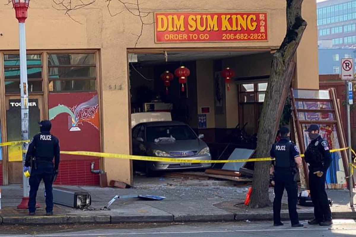 A Toyota Camry sits inside Dim Sum King after it crashed into the restaurant Thursday afternoon, while police officers wait outside and yellow police tape cordons off the area.