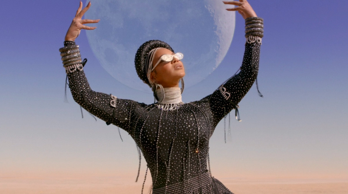 Beyonce in Black Is King, holding up the moon in a desert