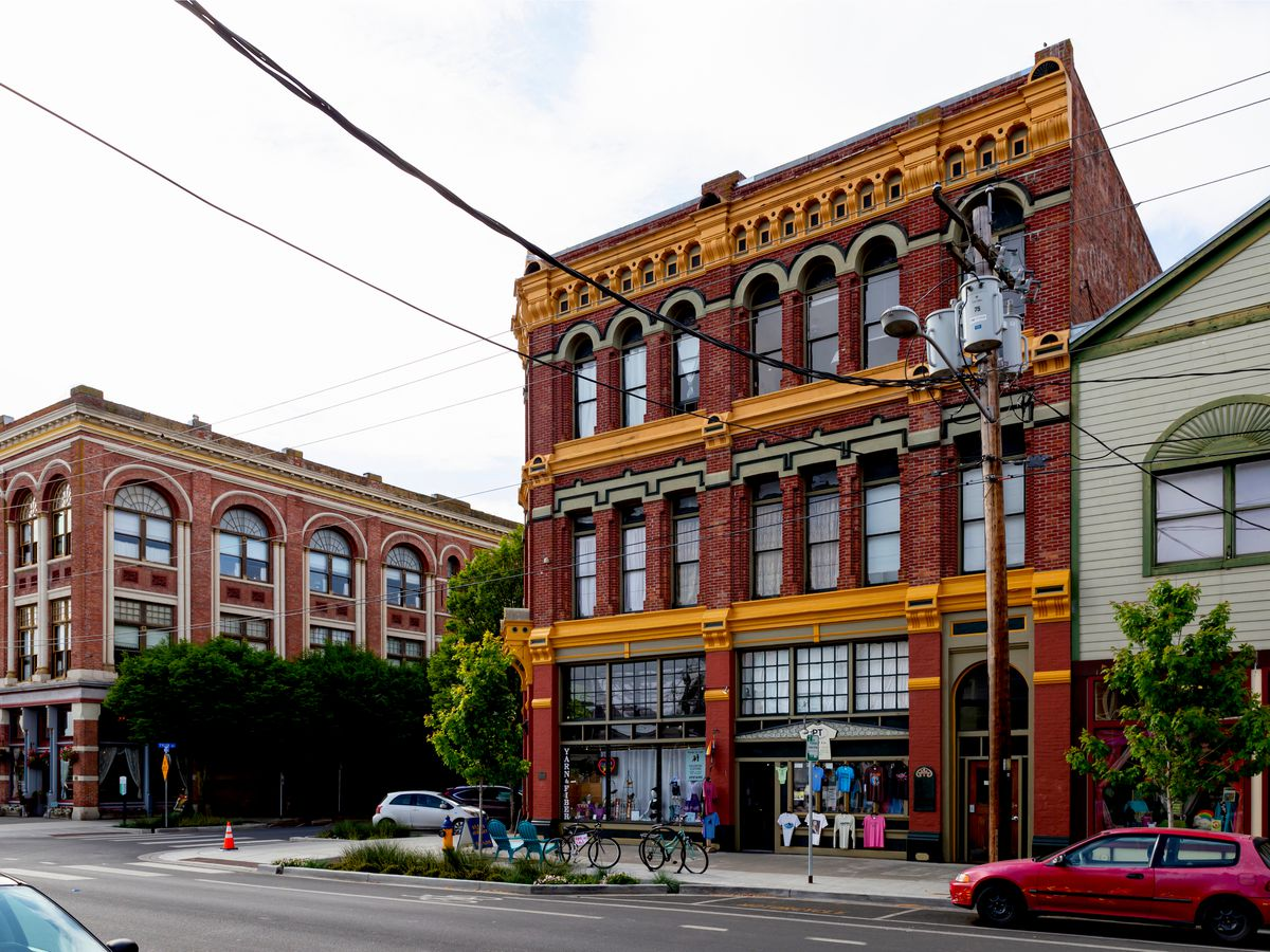 A three-story building with heavy, colorful Victorian ornamentation. A similar building and a gray building with a peaked roof are on either side.