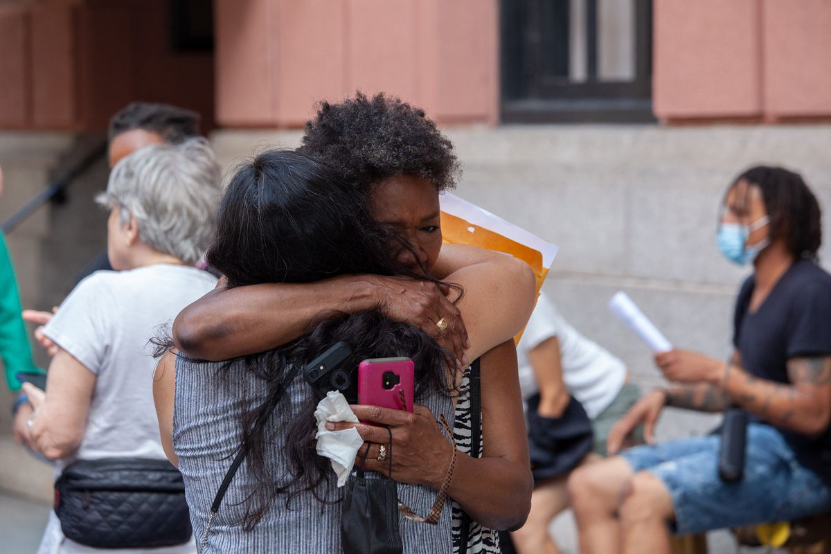 Deputy Public Advocate for Housing Delsenia Glover hugs Corinne Low from the group Upper West Side Open Hearts as homeless men were forced to leave the Lucerne Hotel, June 28, 2021.