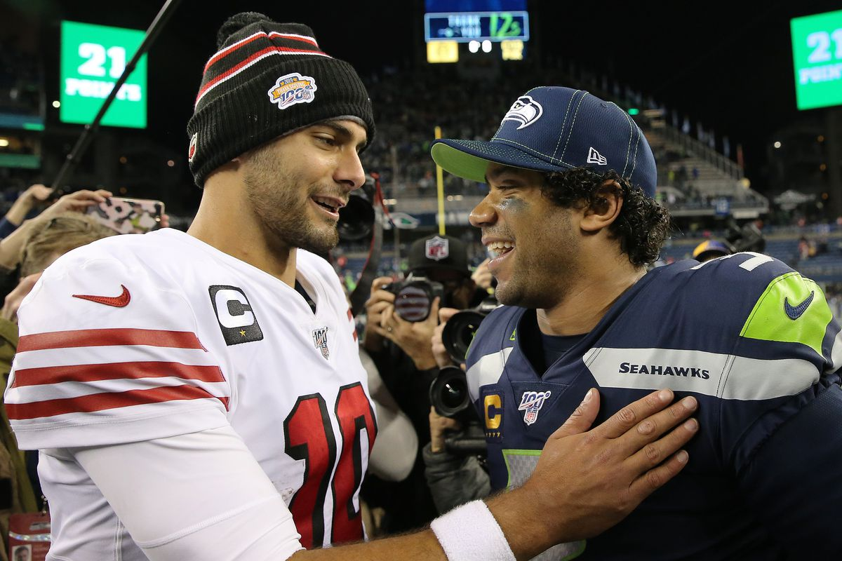 Jimmy Garoppolo #10 of the San Francisco 49ers and Russell Wilson #3 of the Seattle Seahawks hug after the San Francisco 49ers defeated the Seattle Seahawks 26-21 during their game at CenturyLink Field on December 29, 2019 in Seattle, Washington.