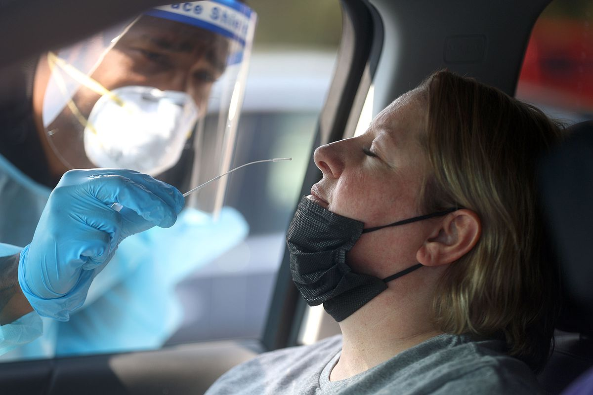Frankie Coelho, a Nomi Health EMT, tests Angela Hiskey for COVID-19.
