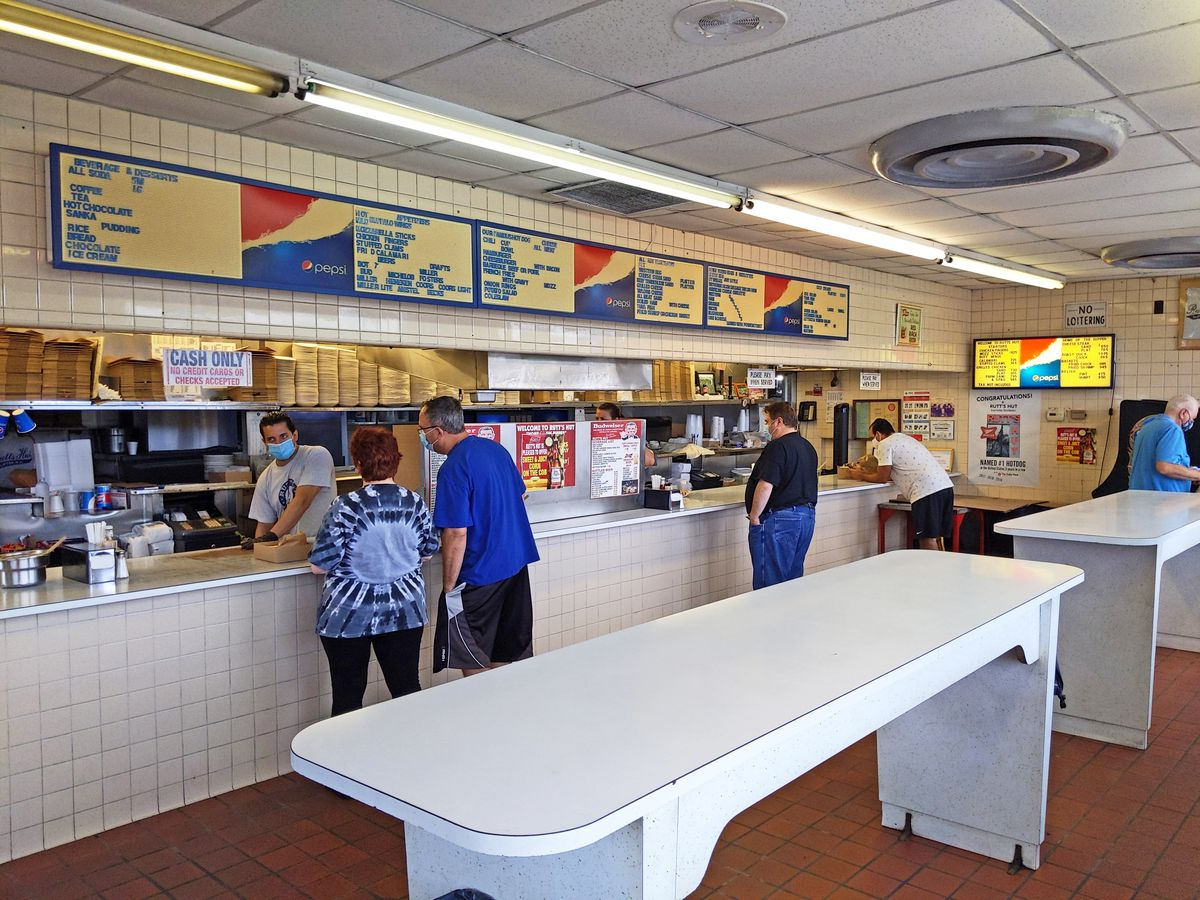 An order counter with clerks behind and customers ordering, with some white standing tables in the foreground.