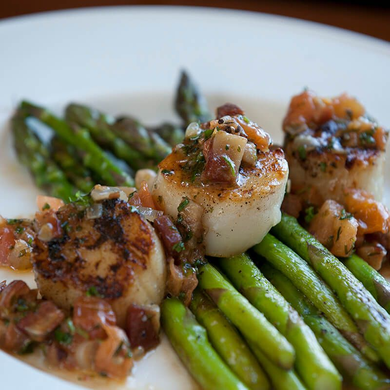 Seared scallops sit atop a pile of asparagus on a white plate