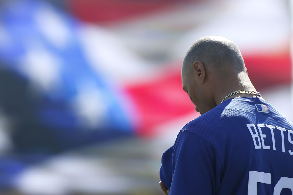 Mookie Betts #50 of the Los Angeles Dodgers during the National Anthem prior to a Cactus League spring training game against the Chicago White Sox at Camelback Ranch on February 24, 2020 in Glendale, Arizona.