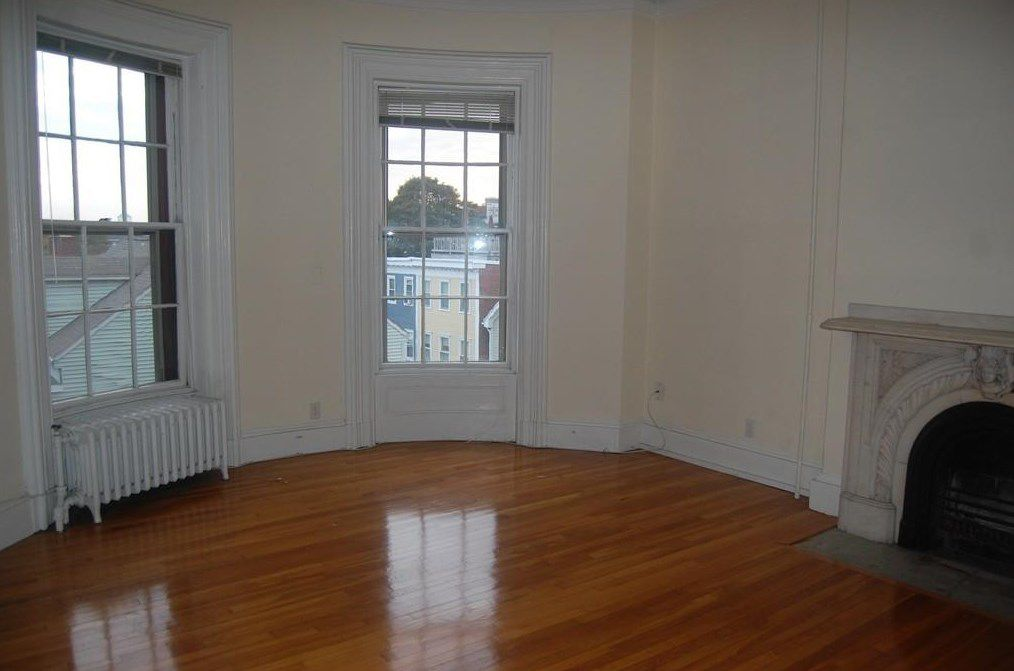 An empty living room with a bow window and a fireplace.