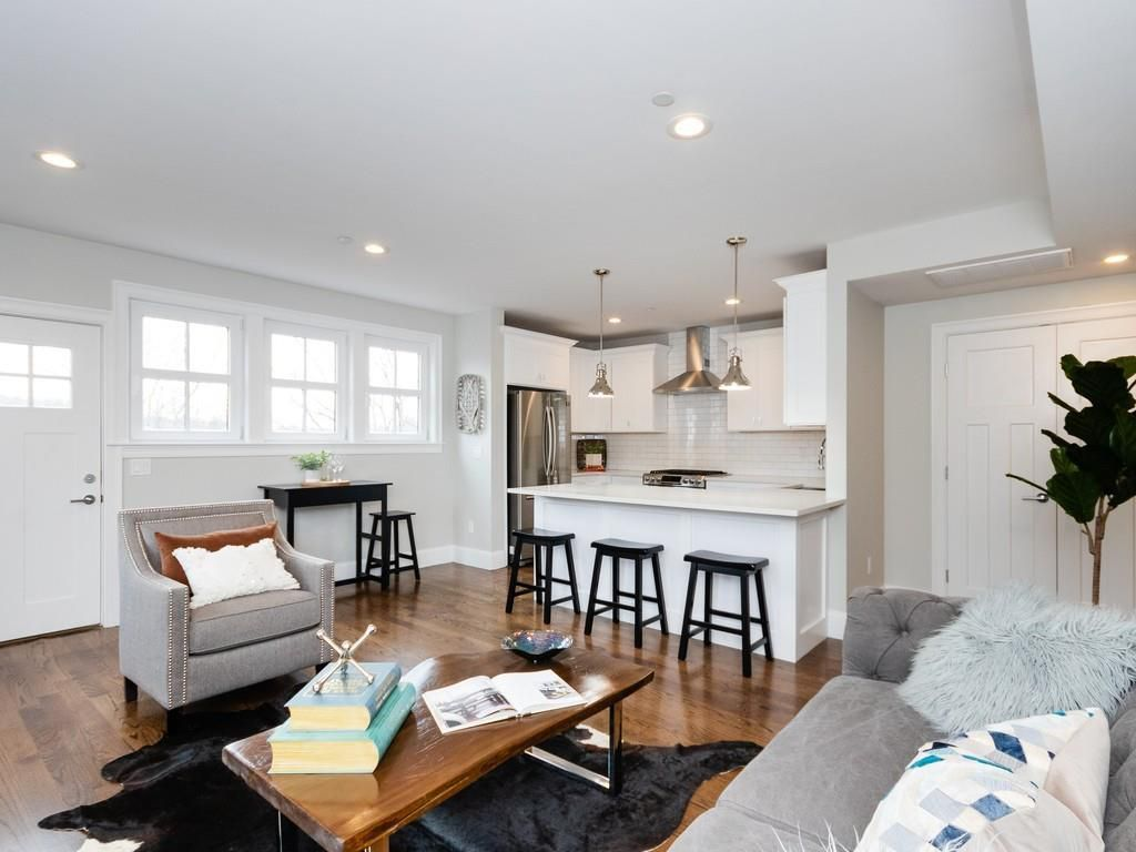 An open living room-kitchen with three stools in front of kitchen island, and there's other furniture.