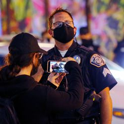 A man takes a photo of a police officer's name tag as a protest at the West Valley City Police Department is disrupted by counterprotesters on Wednesday, Sept. 16, 2020.