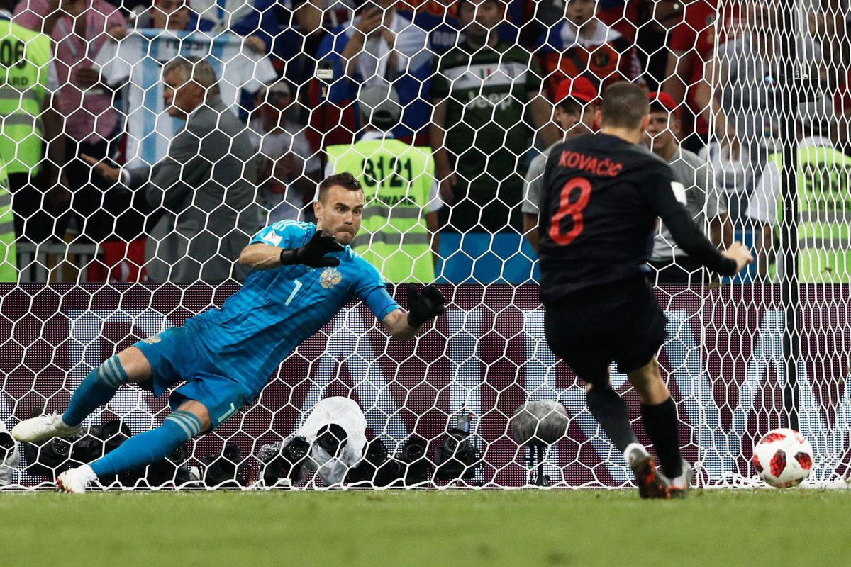 Russian goalkeeper Igor Akinfeev dives to save a penalty from Croatia's midfielder Mateo Kovacic during the Russia 2018 World Cup quarter-final match on July 7, 2018.