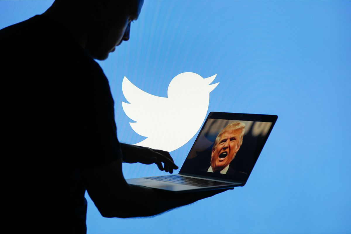 A man is seen with a laptop depicting an image of US president Donald Trump with a Twitter logo displayed in the background.