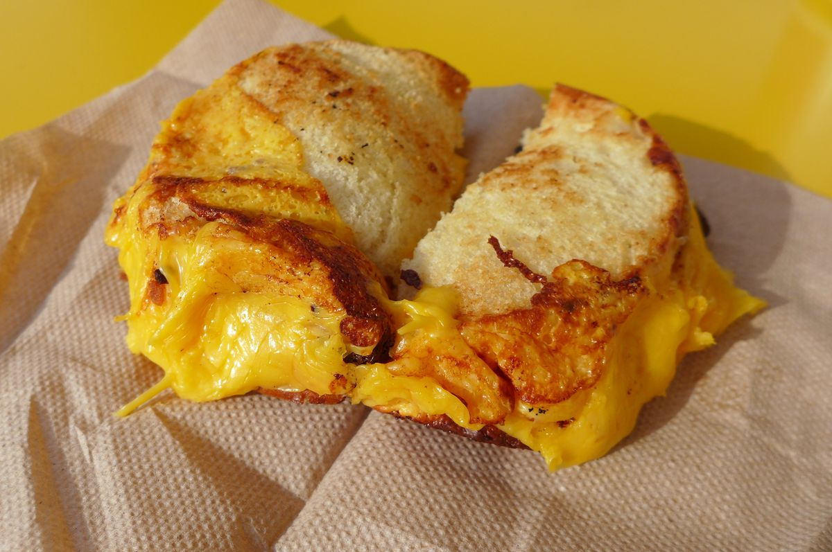 A barely browned sandwich with yellow cheese oozing out on all sides.