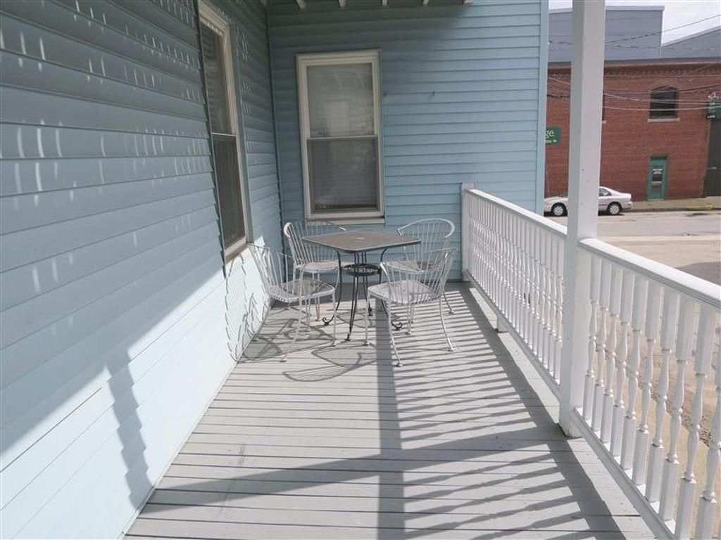 A narrow deck with a small table and chairs at the end.