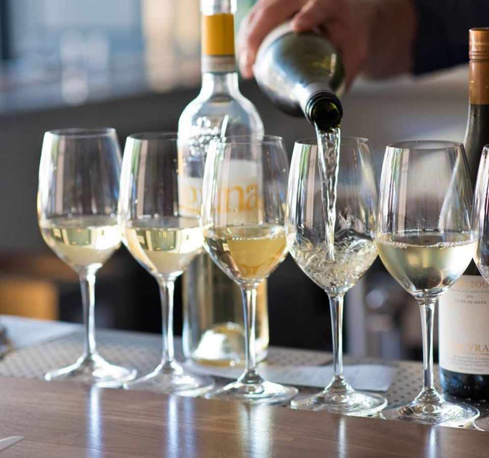 A hand behind the bar at Alma is pouring white wine into a line up of glasses