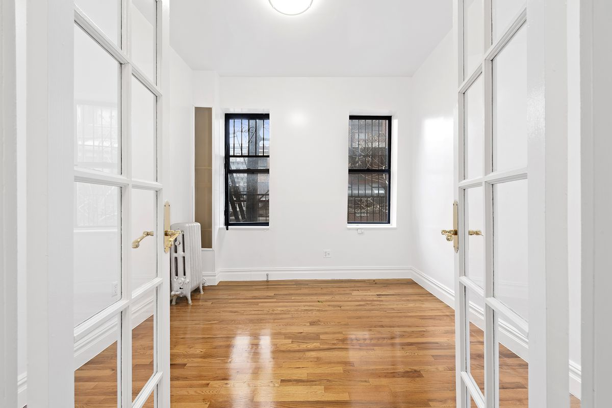 A bedroom with French doors, two windows, hardwood floors, and white walls.