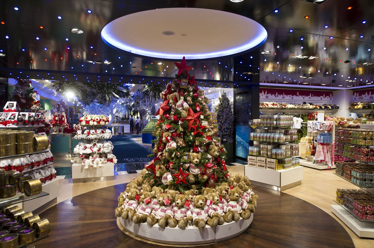 A Christmas tree in a department store display is surrounded by identical teddy bears.