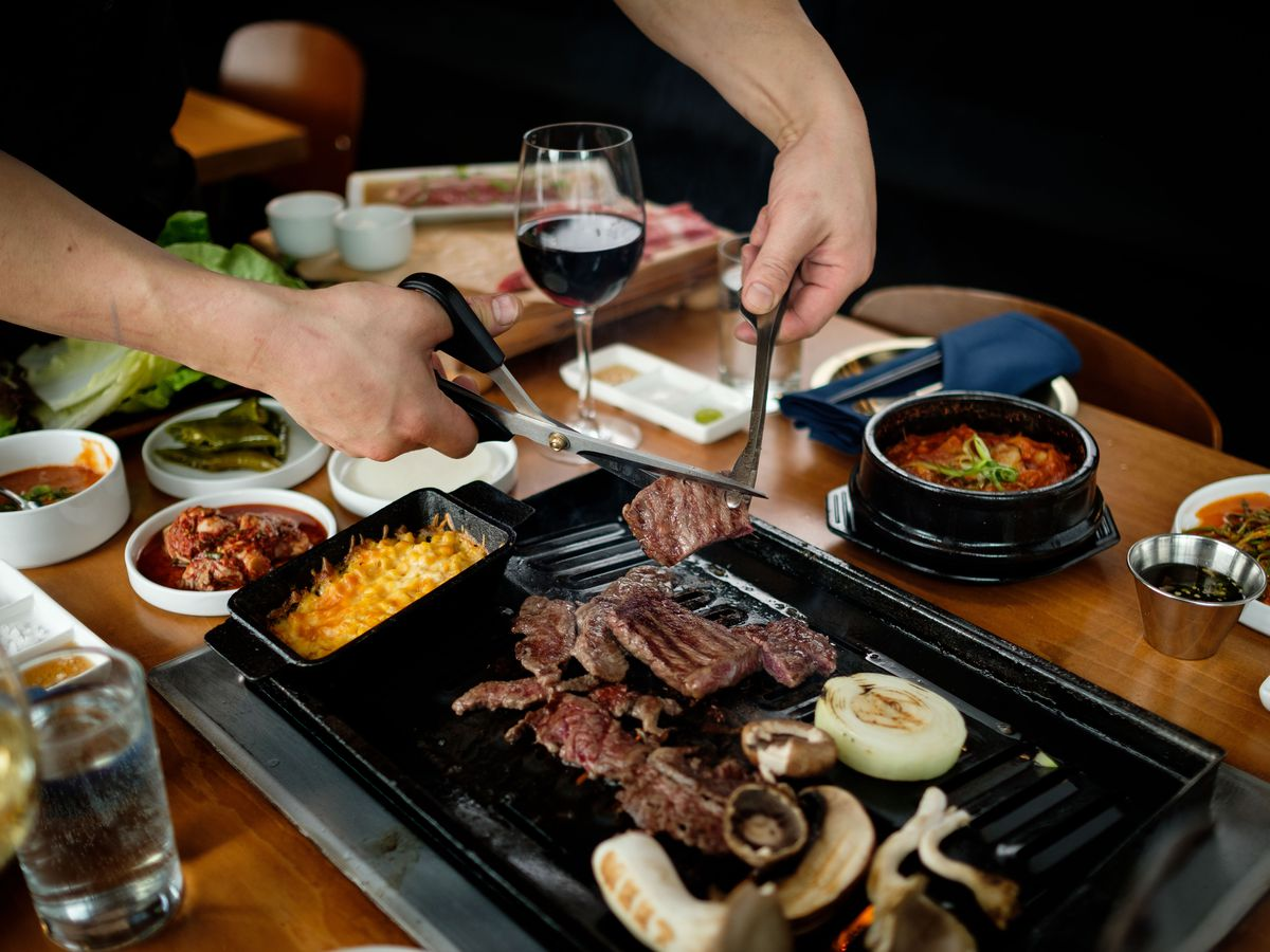 Beef cooking at a Meet Korean BBQ tabletop grill, with the hands of a chef cutting the meat into pieces.