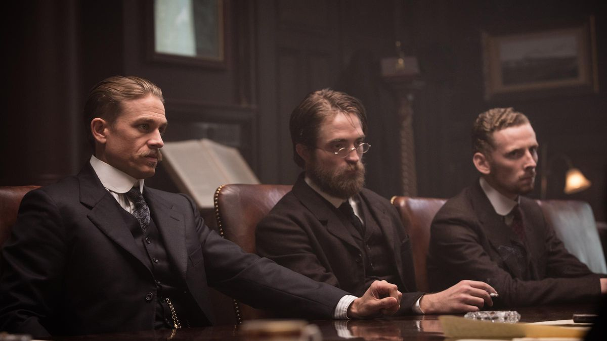 charlie hunnam and robert pattinson at a table in The Lost City of Z