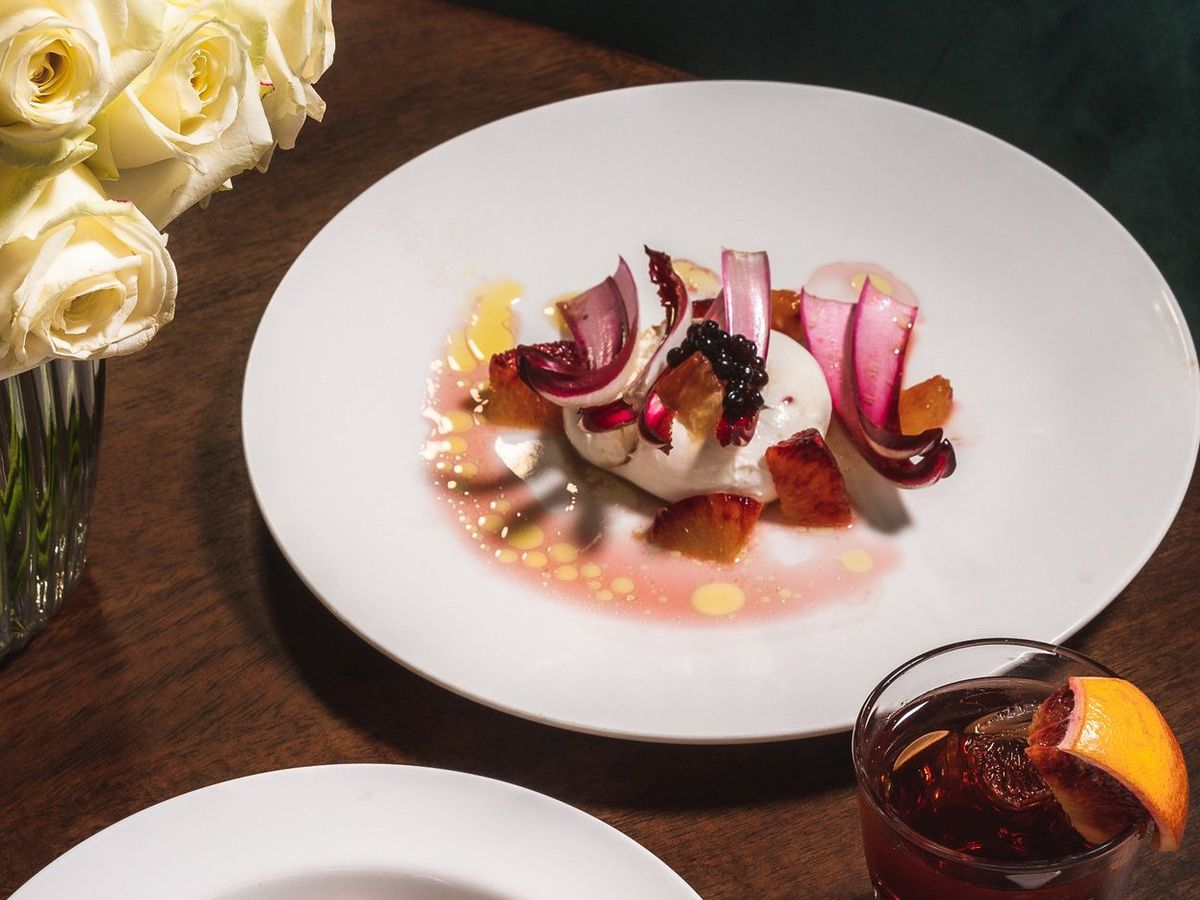 Roses, a negroni, and radicchio with burrata and caviar on a dark wood table