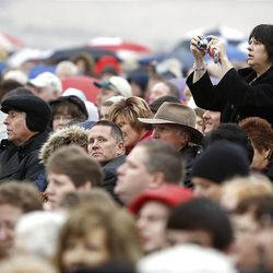A woman stands to take a picture as thousands turn out in the rain Saturday, Oct. 8, 2011 for the ground breaking for the Payson Temple.