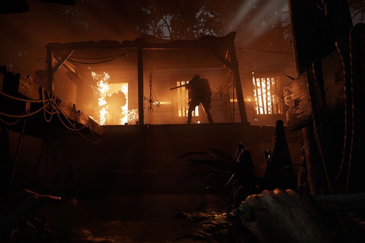 Hunt: Showdown - A figure stands in front of a burning building