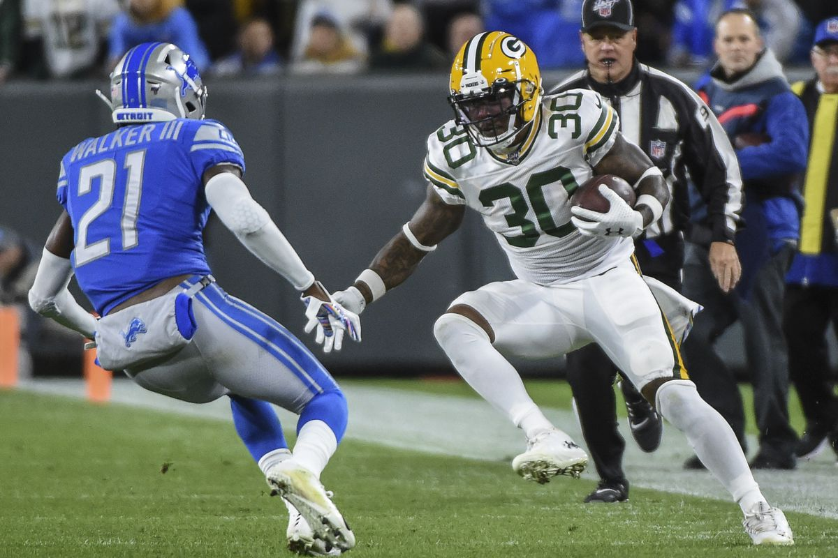 Green Bay Packers running back Jamaal Williams runs with the ball defended by Detroit Lions safety Tracy Walker in the first quarter at Lambeau Field.