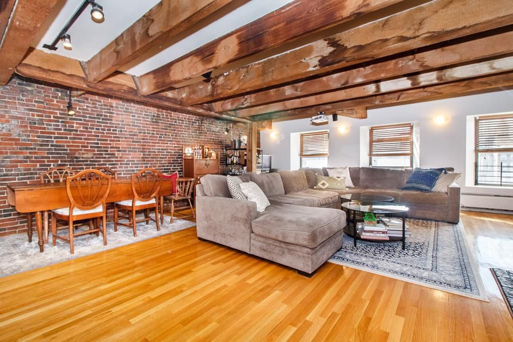 A wide-open living room-dining room with high wood-beamed ceilings and furniture.