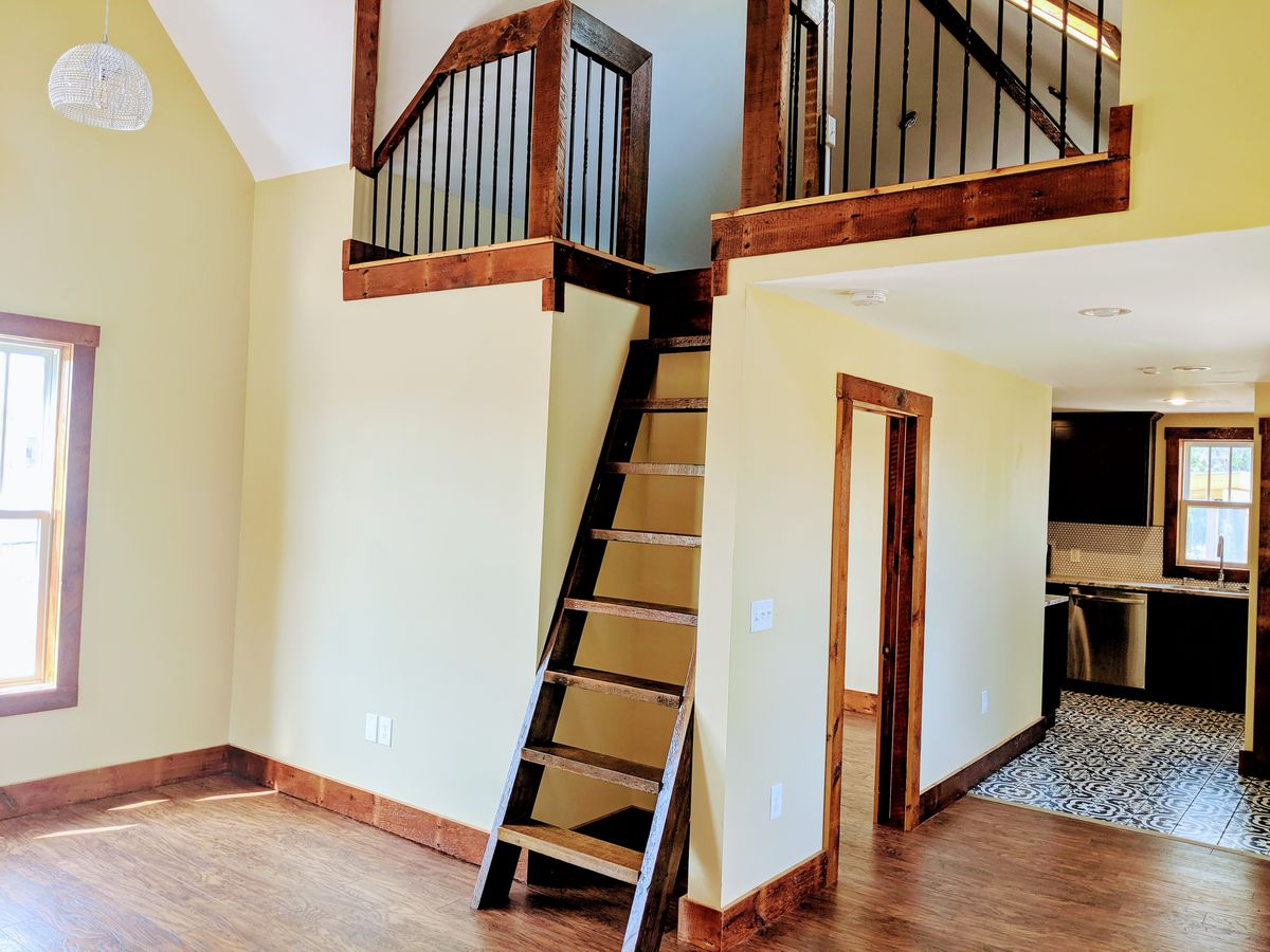 A wood ladder on a hardwood floor leads to an upper space with metal railings. Around the corner there's floral-tiles in the kitchen.