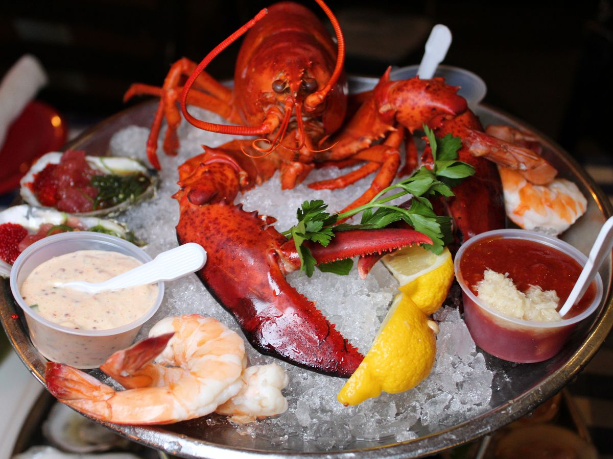 A whole lobster sits on ice in a round tray, surrounded with accoutrements and other bits of seafood