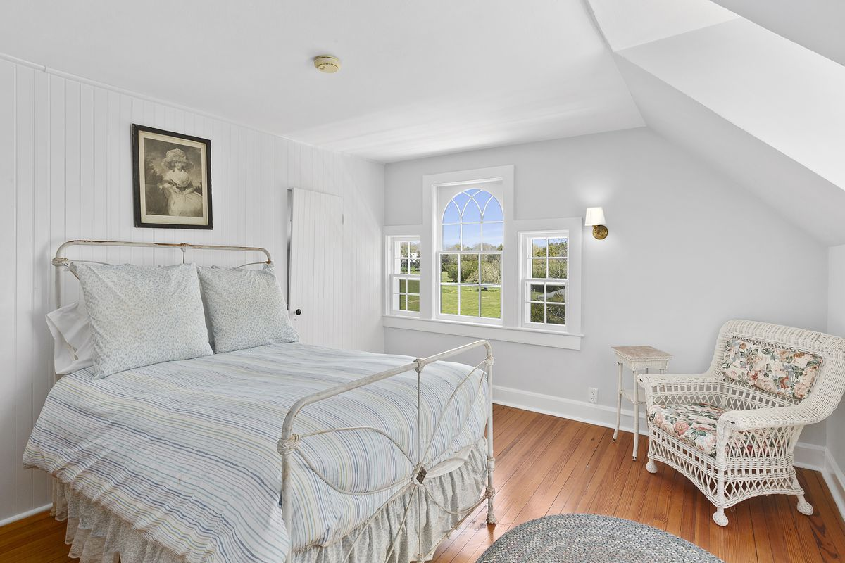 A small white bed in a bedroom with wood floors and a white wicker chair.
