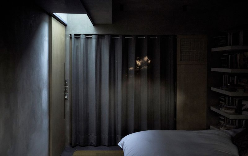 A dark bedroom with drawn curtains and concrete walls. The only light from the room comes from a skylight on the left.
