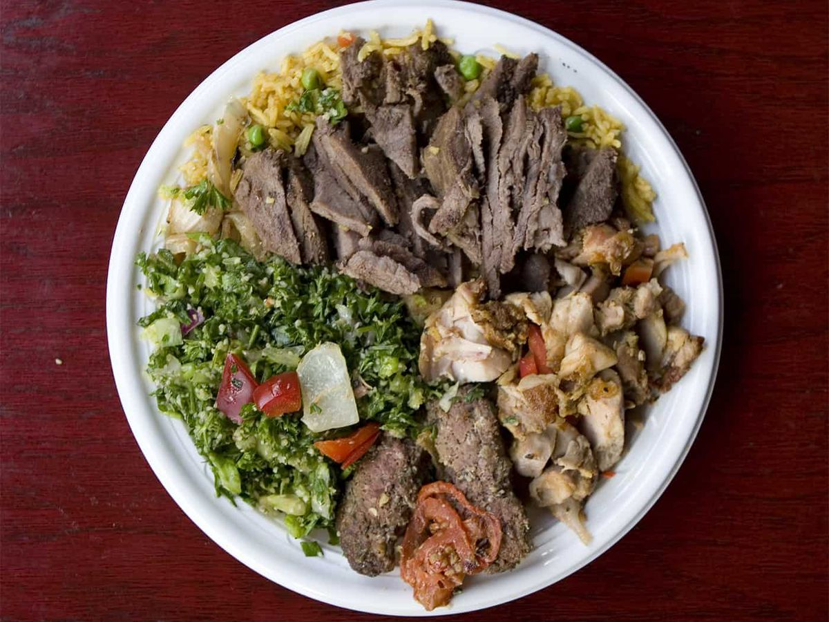 A meat combination plate with rice and salad.