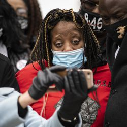 """Clifftina Johnson cries while watching her daughter, Tafara Williams, speak to reporters from her hospital bed via a video conference call during a press conference outside Waukegan's city hall complex, Tuesday morning, Oct. 27, 2020. Williams, 20, was wounded and her boyfriend, 19-year-old Marcellis Stinnette, was killed when they were both shot by a Waukegan police officer on Oct. 20. Three days after the incident, Waukegan Police Chief Wayne Walles announced that he had fired the officer, saying he'd committed """"multiple policy and procedure violations."""""""